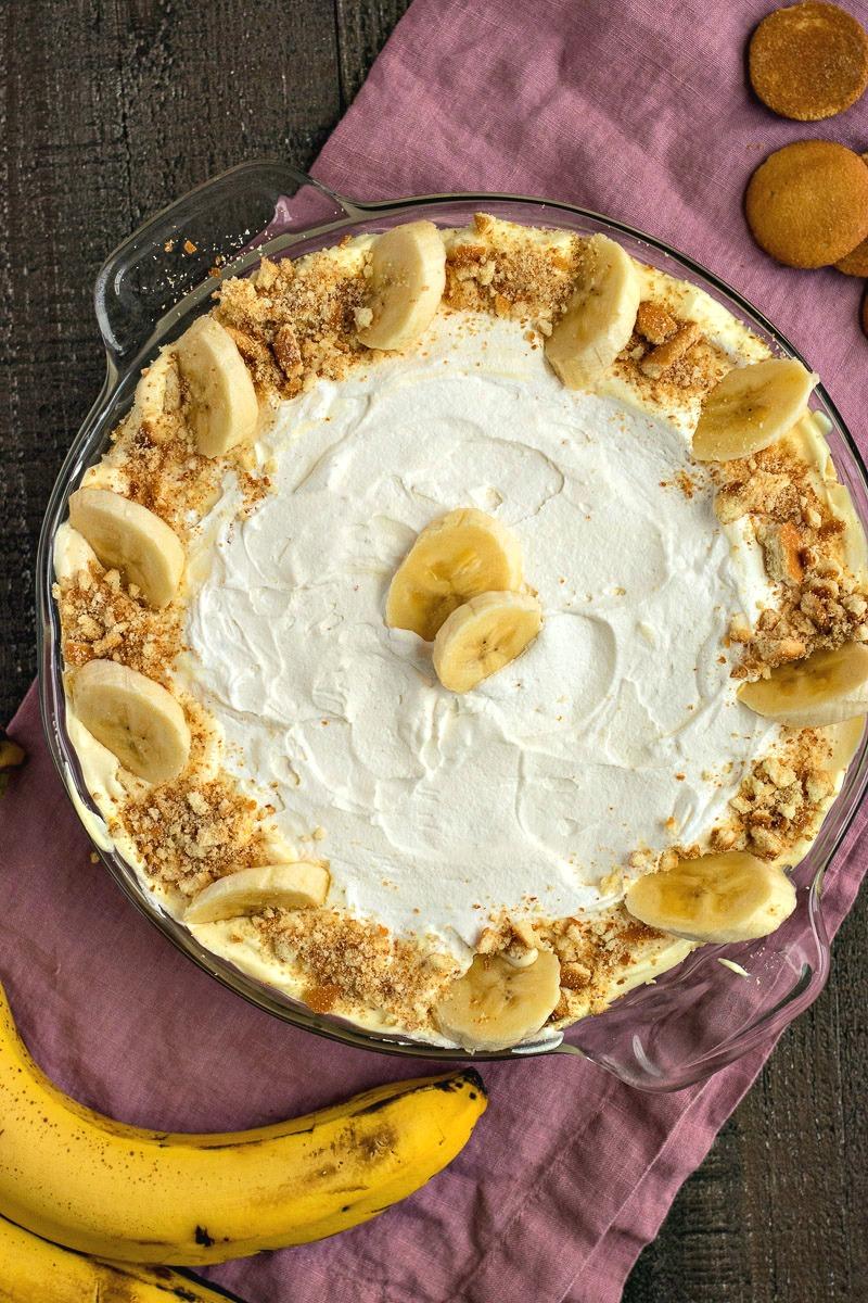 Pie dish of Banana Cream Pie Dip with banana slices and crushed wafers around the edge