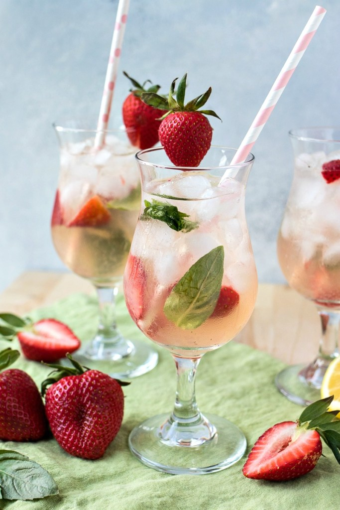 glasses of strawberry basil vodka punch on top of a cloth napkin with strawberries and a sliced lemon next to them, shot from a side angle