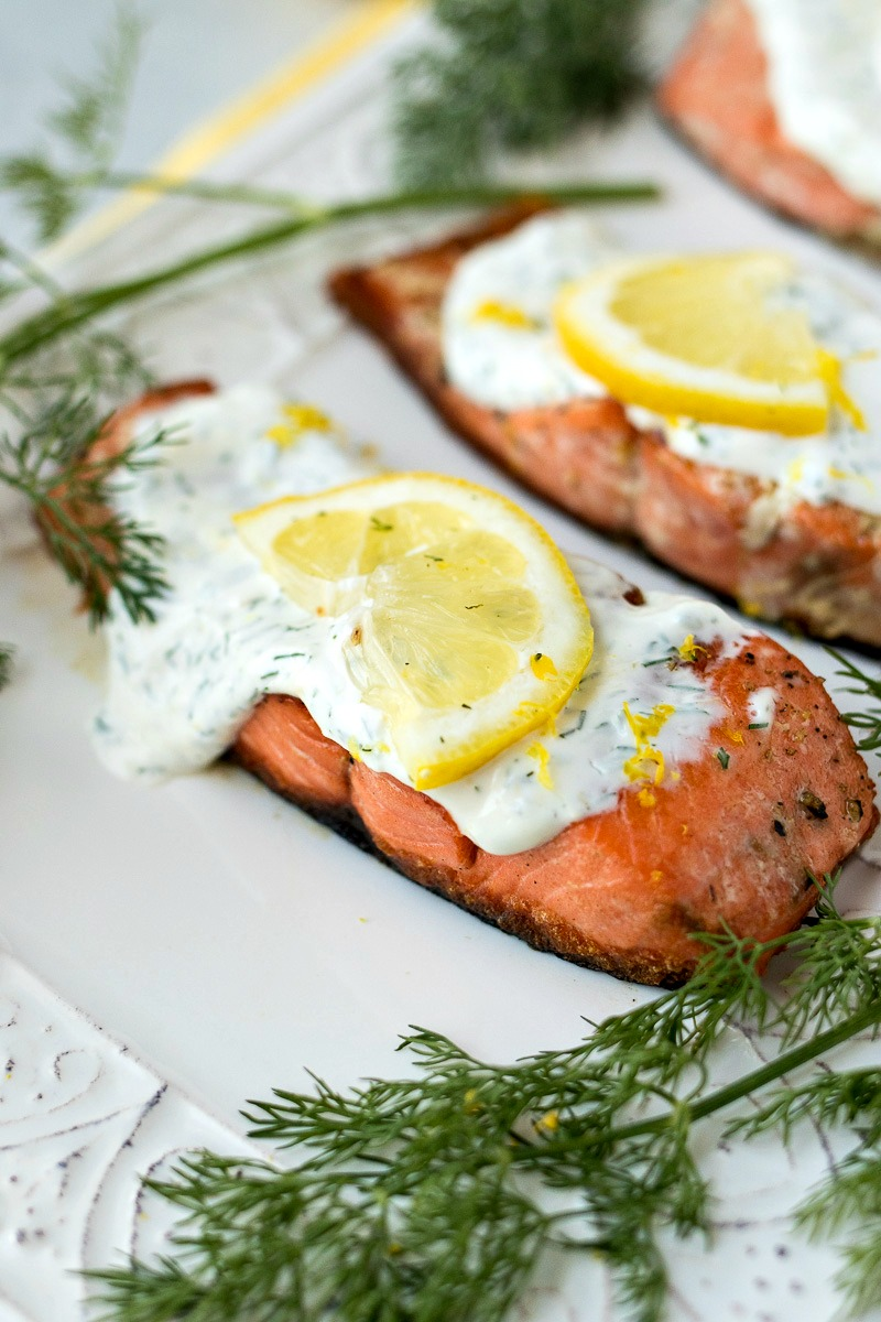 Creamy Dill Salmon covered in dill sauce with a slice of lemon