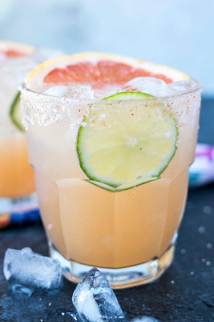 two glasses of palomas with ice and a lime and grapefruit slice in it with ice sprinkled around it, shot from a side angle