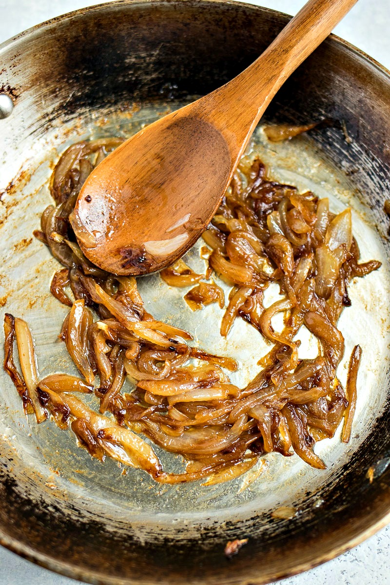 Stirring the caramelized onions with a wooden spoon