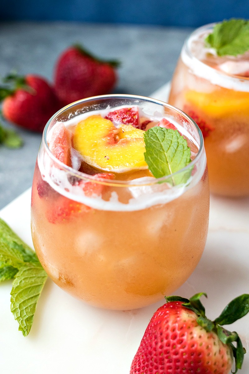Glass of Strawberry Peach Sangria with a peach and lemon slices in it