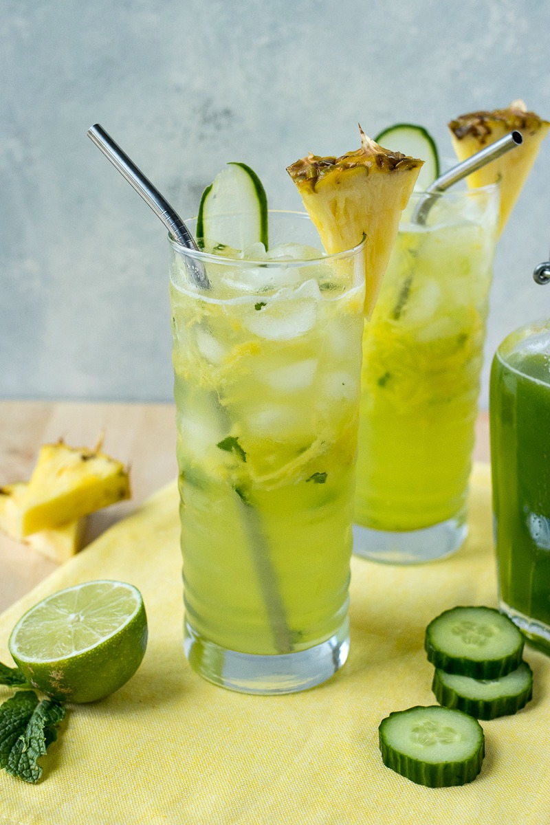 Two tall glasses of Cucumber Pineapple Gin Refresher with pineapple garnish
