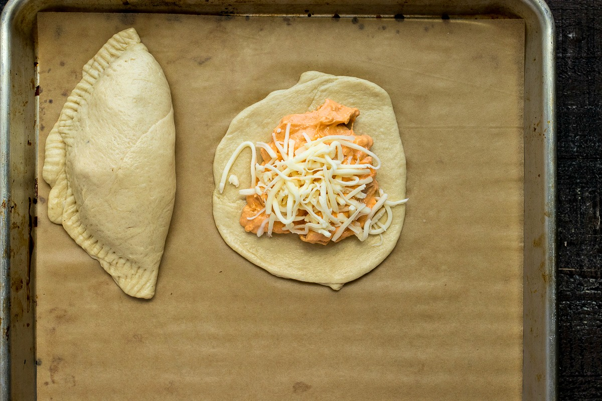 Buffalo Chicken Pocket dough being filled with chicken, sauce mixture and shredded cheese