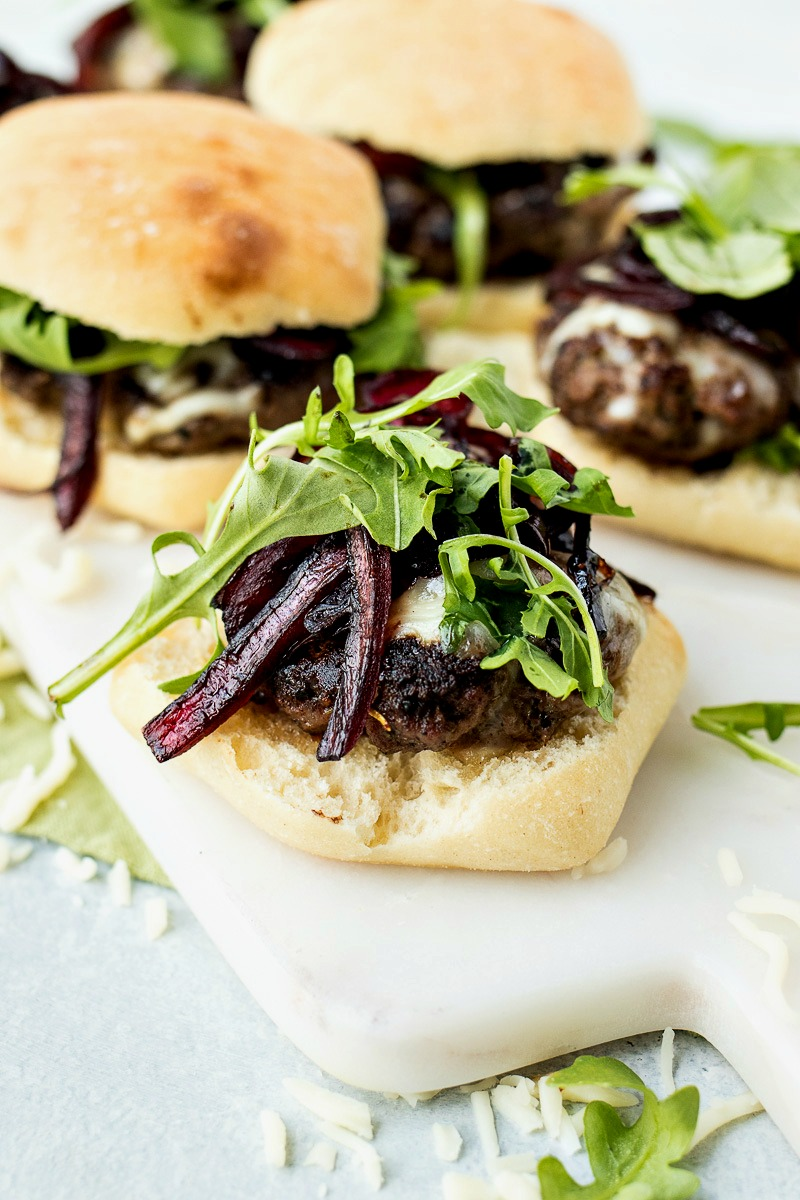 Italian Cheeseburger Sliders with the top of the ciabatta roll off to show the arugula and caramelized onions