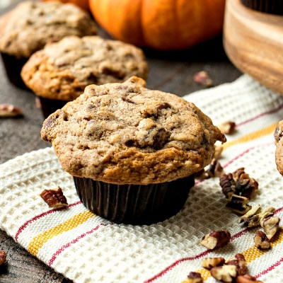 staged shot of pumpkin cinnamon crunch muffins with sprinkled pecans and pumpkins in the background, shot from a side angle