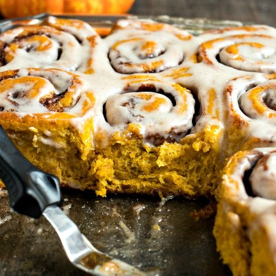 a glass dish with pumpkin cinnamon rolls in it with some missing from the center and a spatula with a pumpkin the background, shot from a side angle