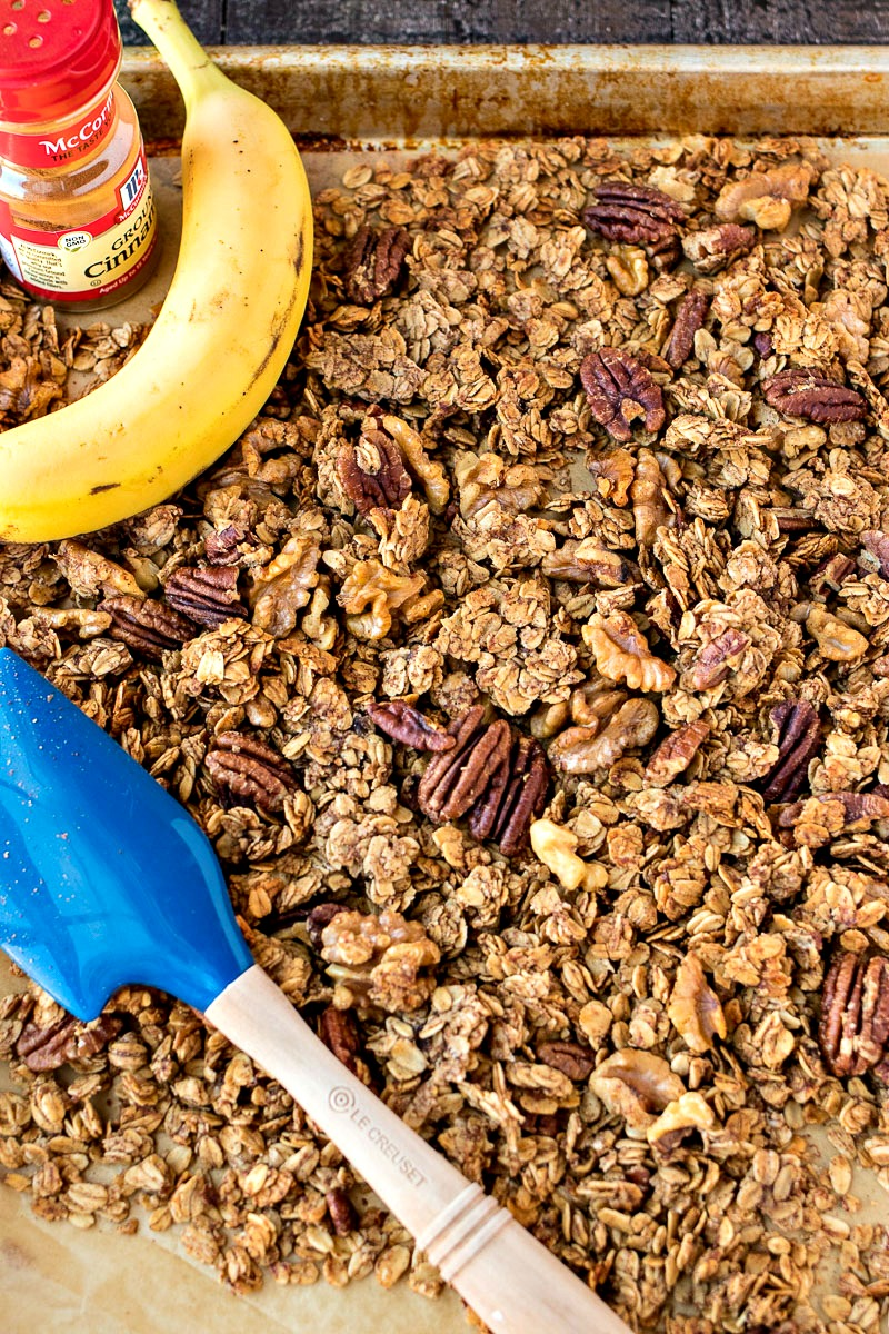 Cookie sheet of Banana Bread Granola with a banana, ground cinnamon and a spatula