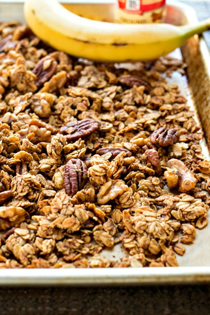 a baking sheet with banana bread granola a whole banana and a bottle of cinnamon on it, shot from a side angle