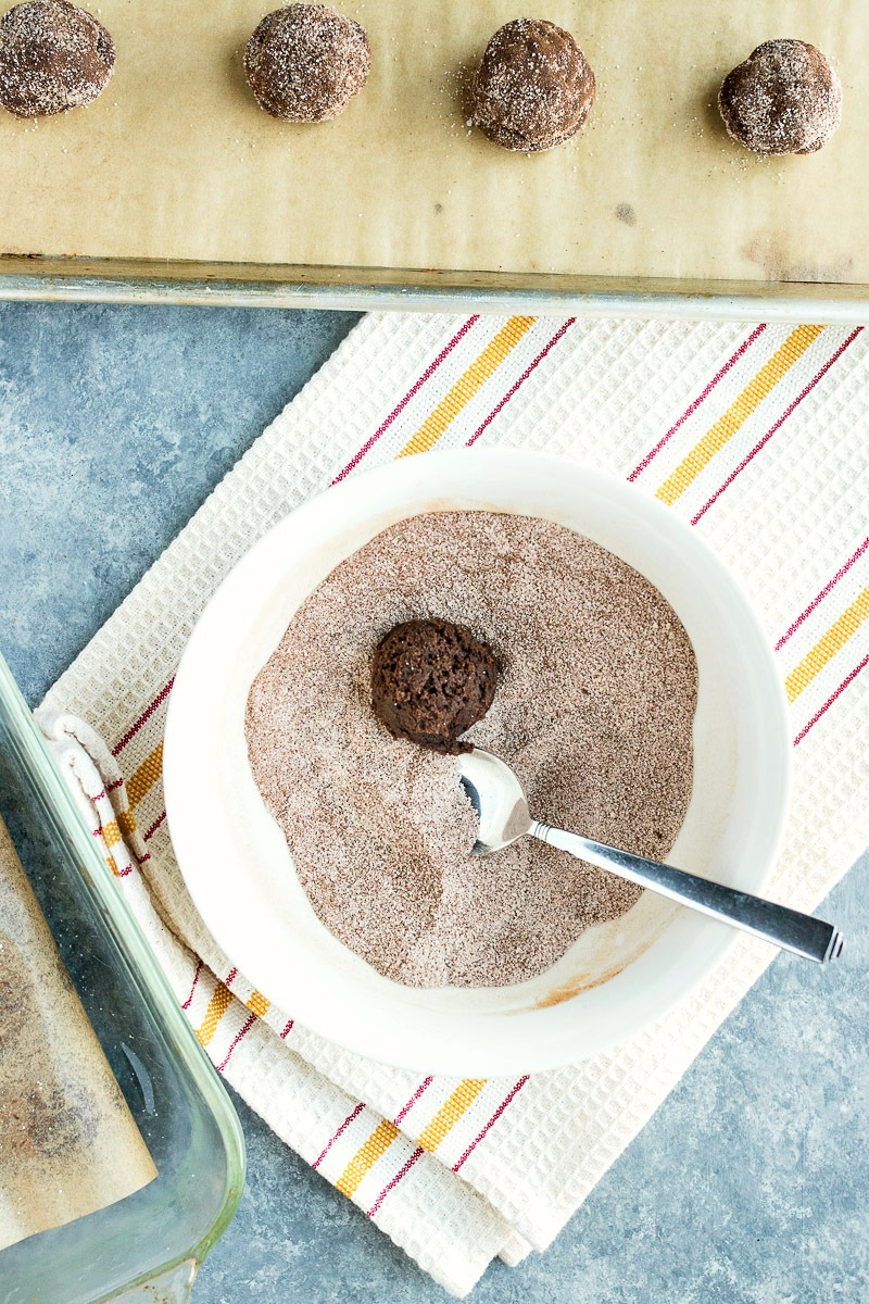 Rolling chocolate cookie dough ball in cinnamon sugar
