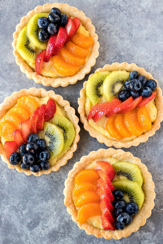 four mini fruit tarts, shot from overhead