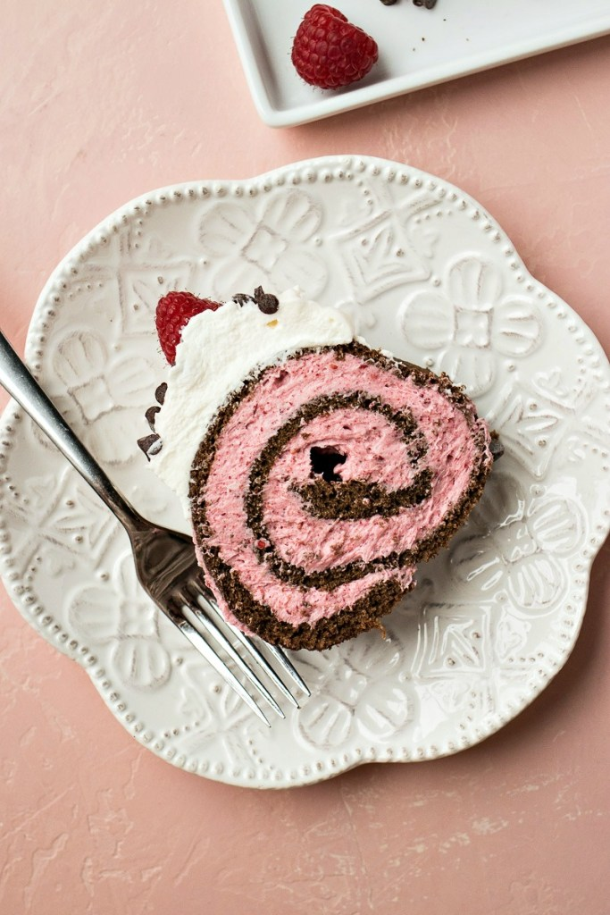 plate of a slice of chocolate raspberry cake roll with a fork and a platter with a whole raspberry on it, shot from overhead