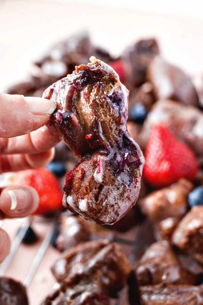 fingers holding a chocolate berry fritter with a wire rack with more fritters and mixed berries surrounding them, shot from a side angle