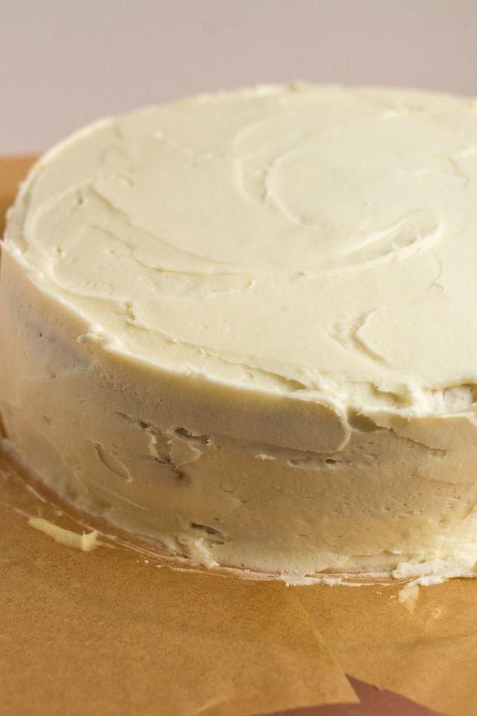 Icing the multiple layers of white cake and coconut cream filling with a coconut cream cheese frosting