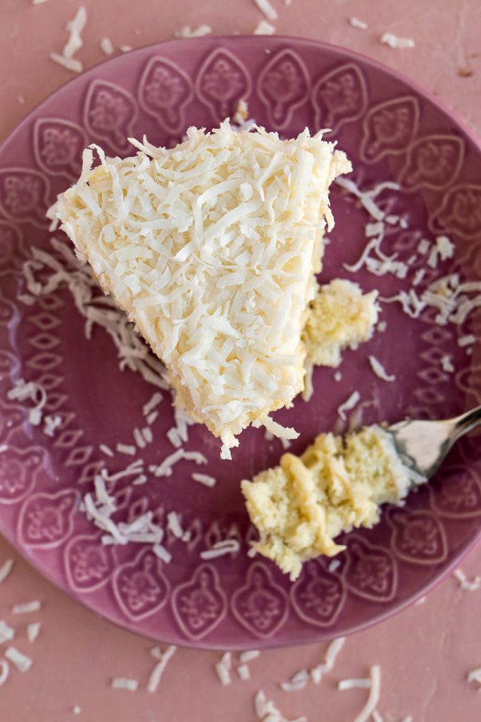 Plate with a piece of Coconut Cream Cake and a forkful of the cake