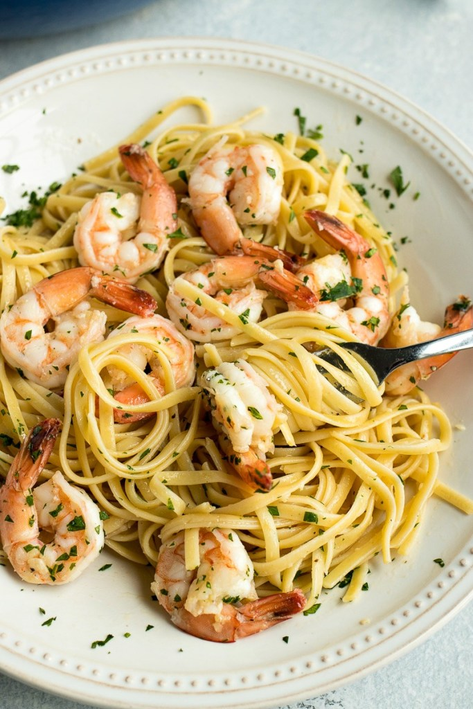 Fork twirling linguine pasta onto it with a shrimp on the end