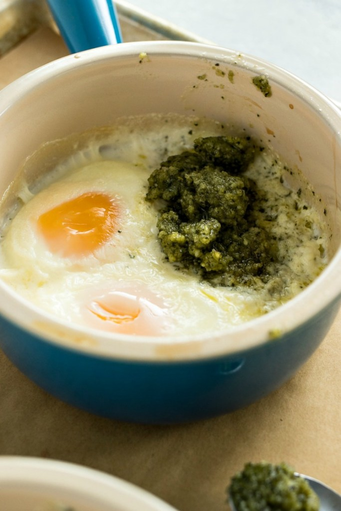 Bowl of baked pesto eggs with the egg white and yolk on one side and the pesto on the other