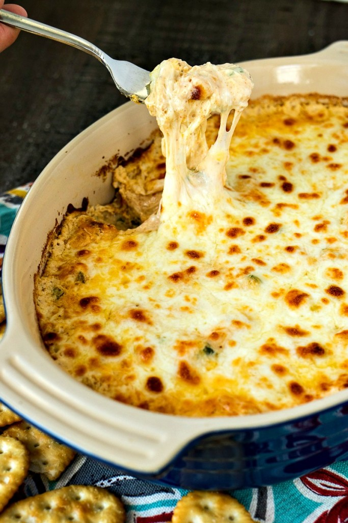 Forkful of cheesy crab dip with cheese stretching from the dip to the fork