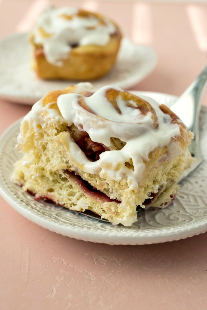 Using a spatula to serve a Raspberry Sweet Roll iced with a tangy icing