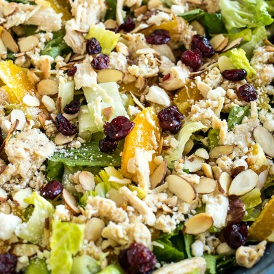 zoomed in shot of citrus almond salad on a trivet, shot from a side angle