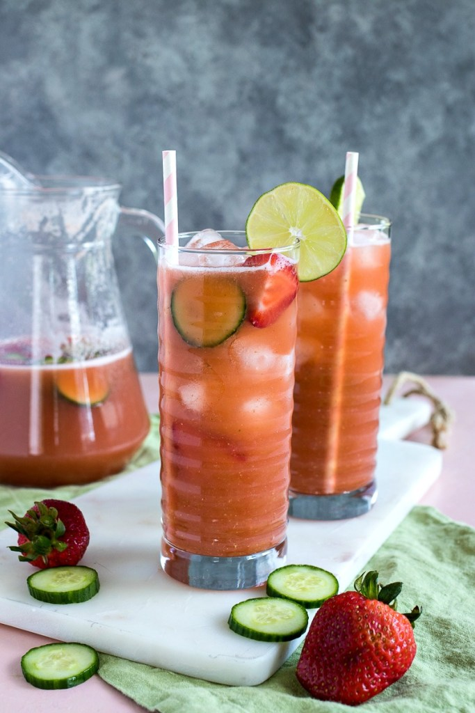 Two glasses of Strawberry Cucumber Limeade in front of a pitcher of Strawberry Cucumber Limeade