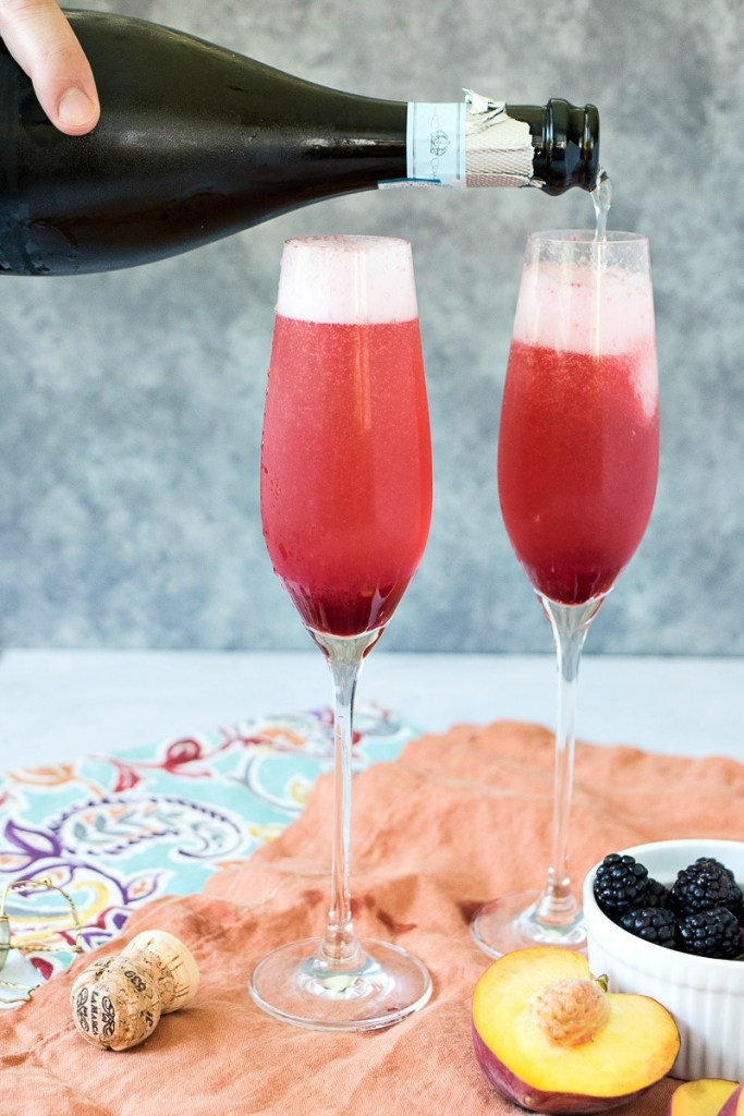 Adding champagne to the glass of fruit puree