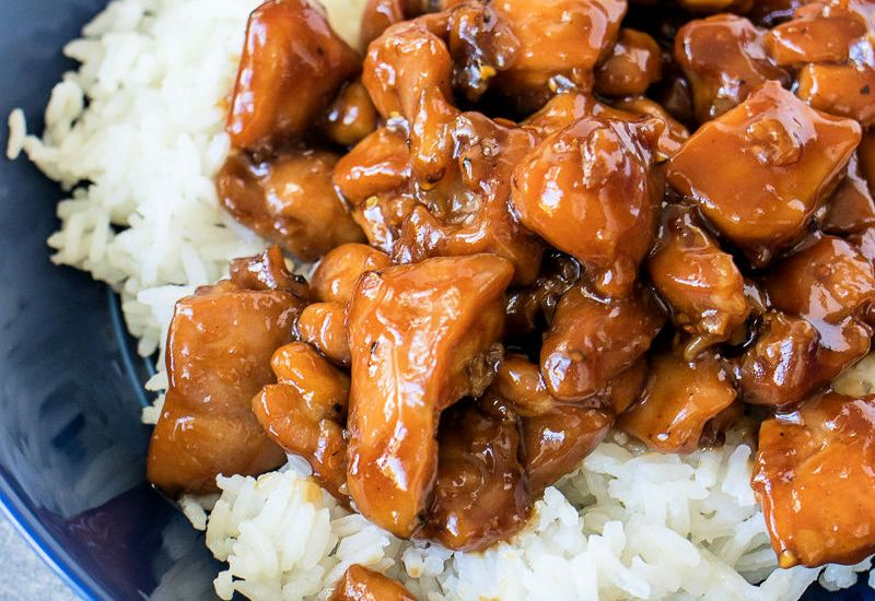 bourbon chicken over rice on a blue plate