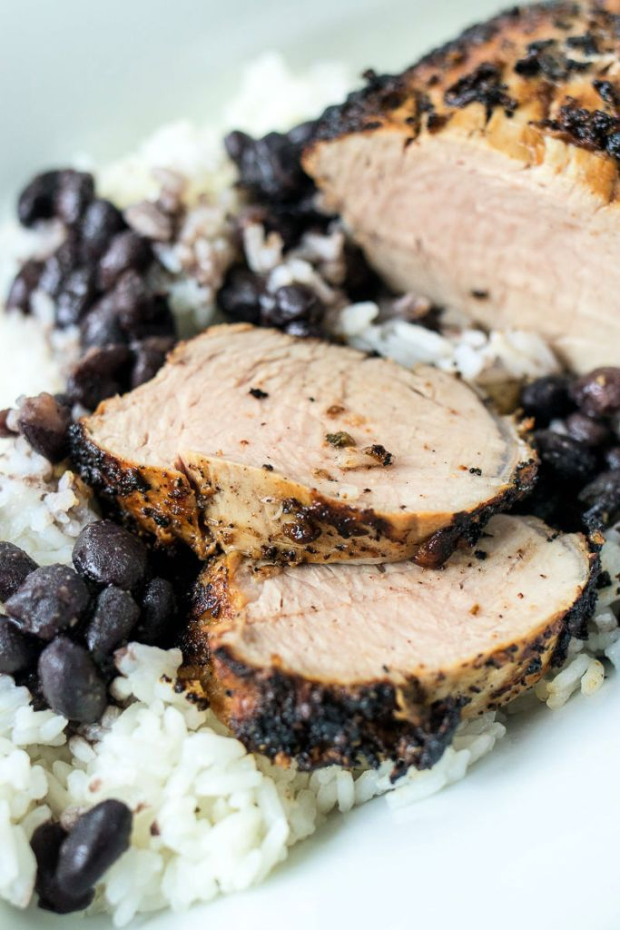 zoomed in shot of sliced mojo pork tenderloin medallions on a bed of rice and black beans