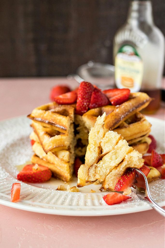 Forkful of waffles in front of the stack of waffles and strawberries