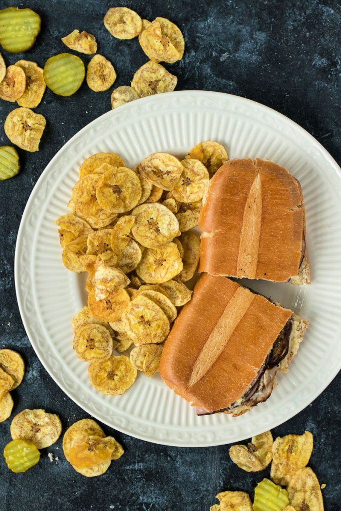 overhead, zoomed out shot of Cuban sandwich cut in half on a large plate with plantain chips
