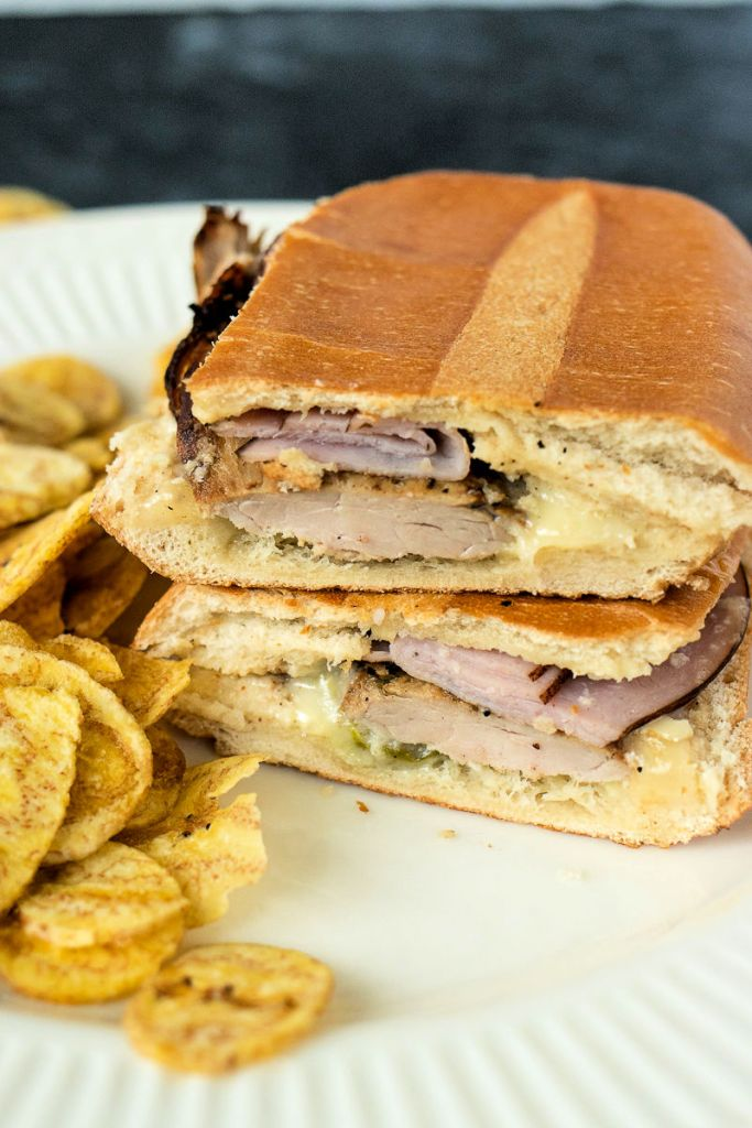 zoomed angled shot of a Cuban sandwich cut in half with the two halves stacked on top of each other, sitting on a plate with plantain chips