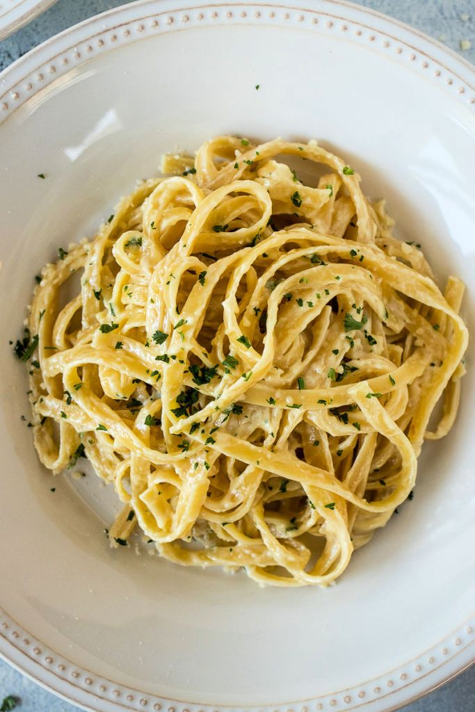 overheat shot of fettuccine alfredo pasta in a shallow dish and chopped parsley sprinkled on top