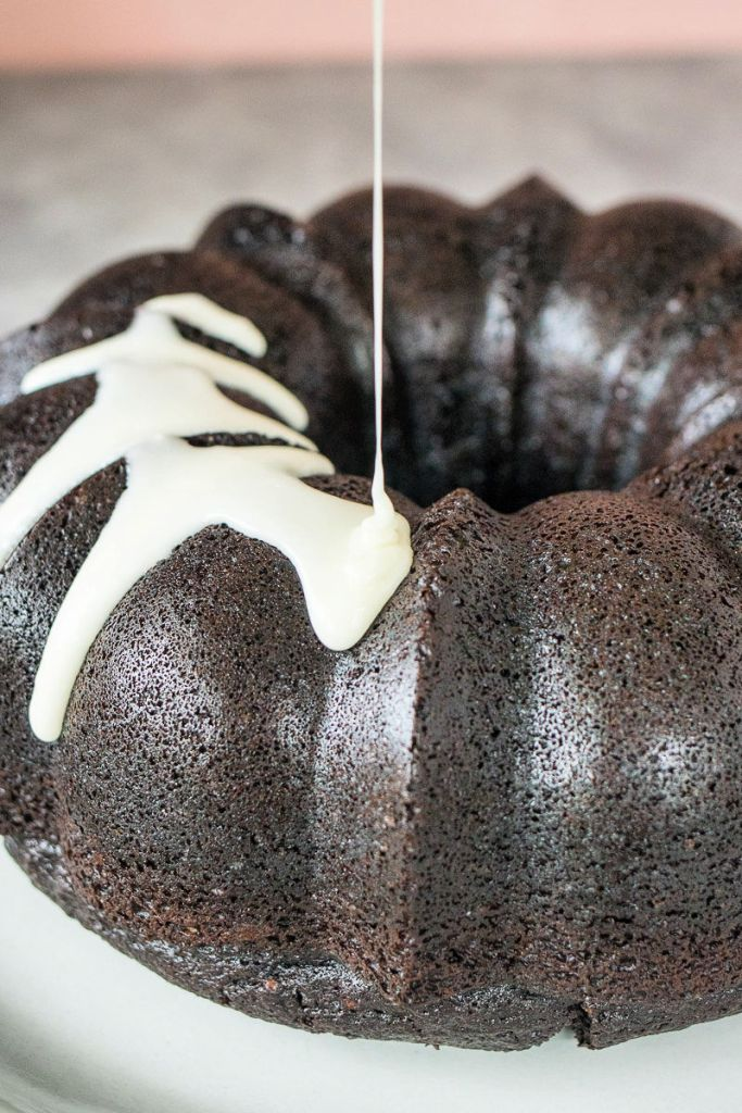 zoomed in shot of icing getting poured over the top of the chocolate bundt cake