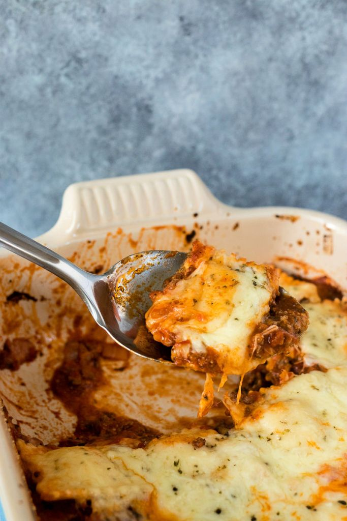 angled shot of easy ravioli lasagna in casserole dish with 2 scoops removed and a serving spoon scooping out another serving