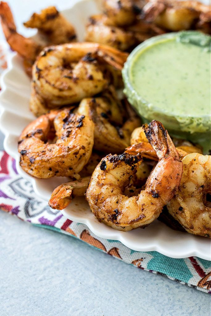 zoomed shot of grilled spicy shrimp sitting on a serving plate with cilantro dipping sauce in the background