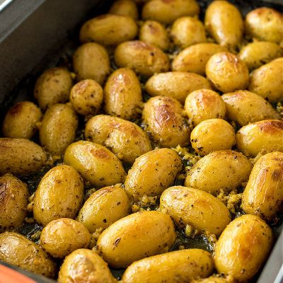 photo taken from the right side of oasted greek lemon potatoes sitting in a dark 9x13 pan