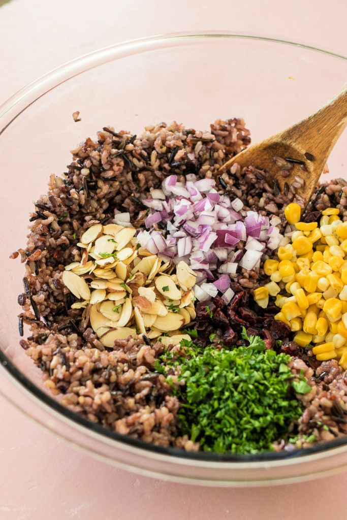 shot of all wild rice salad ingredients in a clear bowl before combining together