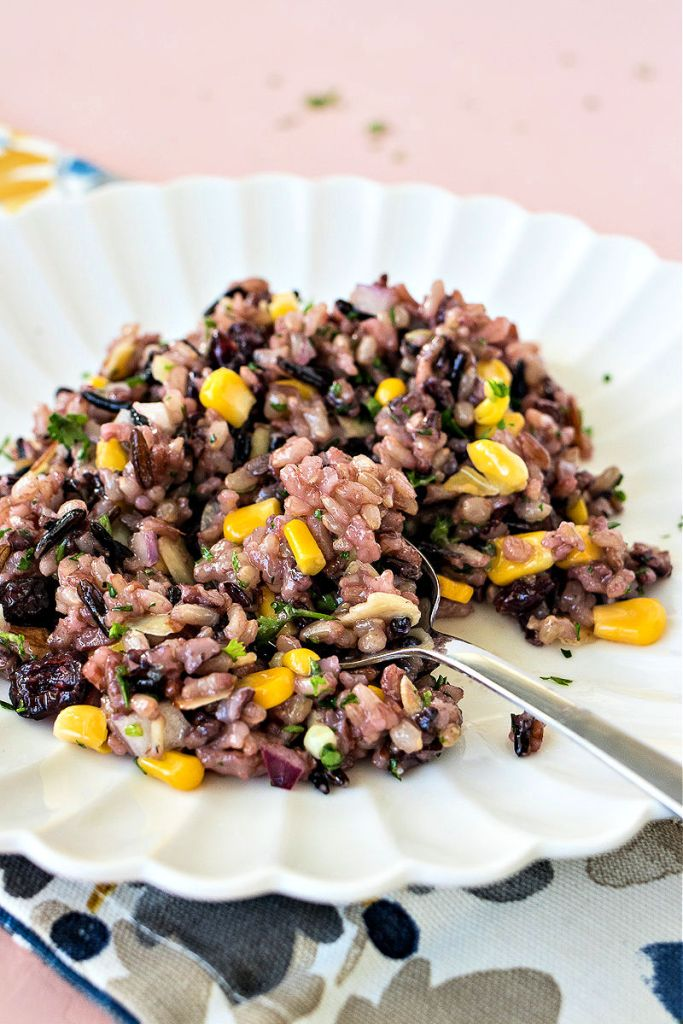 photo of wild rice salad on a white plate with a spoon set in the center