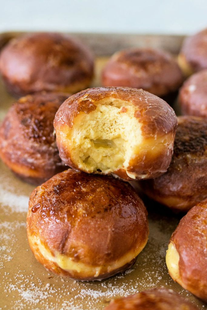 photo of creme brulee doughnuts stacked together with the top doughnut missing a bite