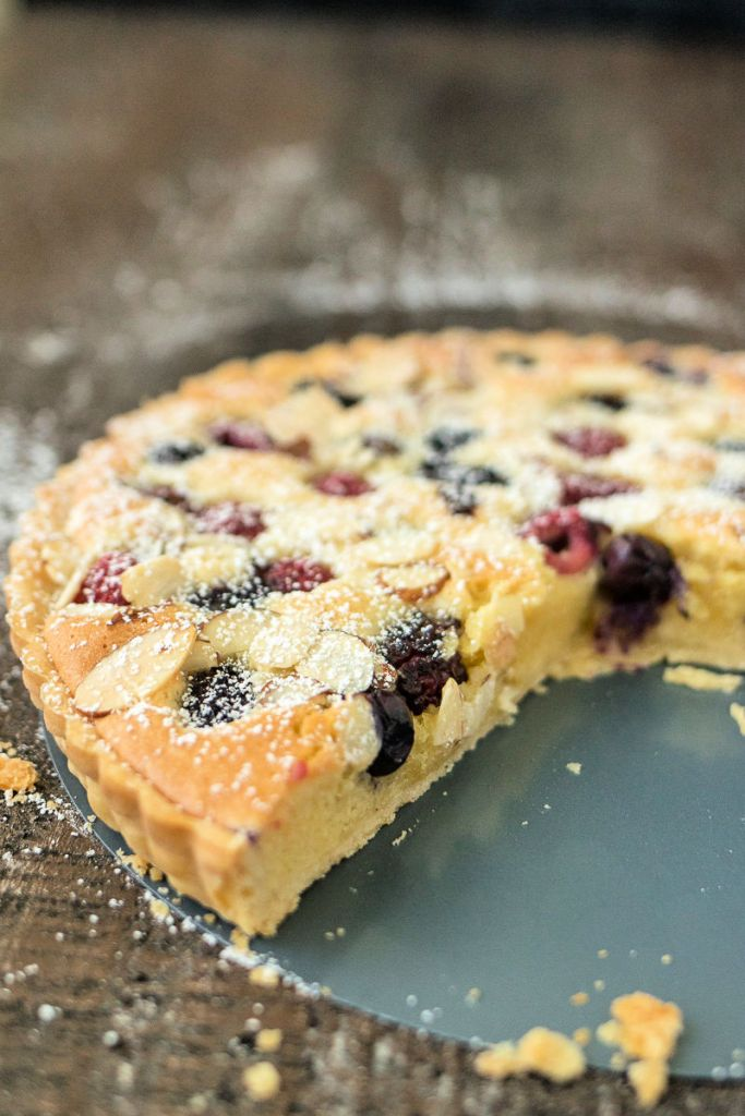 photo of mixed berry almond tart with a few slices removed