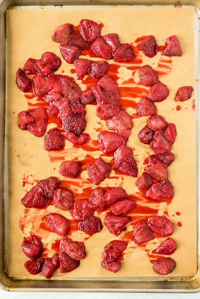 overhead shot of roasted strawberries spread on a baking sheet to cool