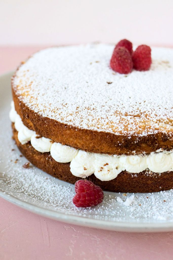 a shot of a whole victoria sandwich cake on a plate with raspberries on top
