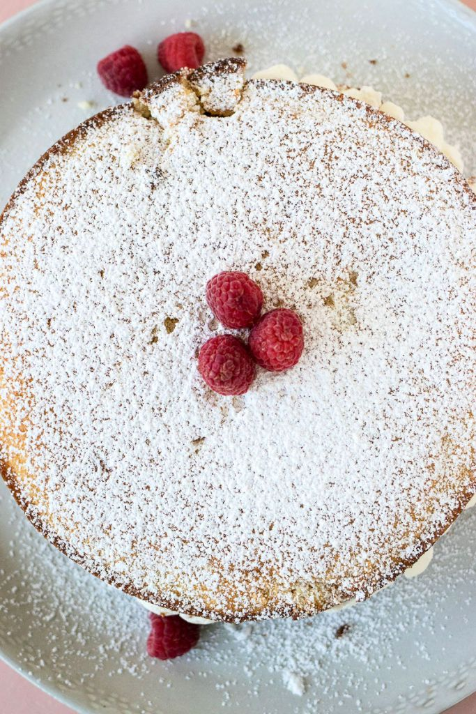 overhead shot of victoria sandwich cake dusted with powdered sugar and raspberries for garnish