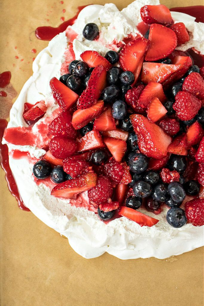 close up overhead shot of berry pavlova sitting on a baking sheet with parchment paper