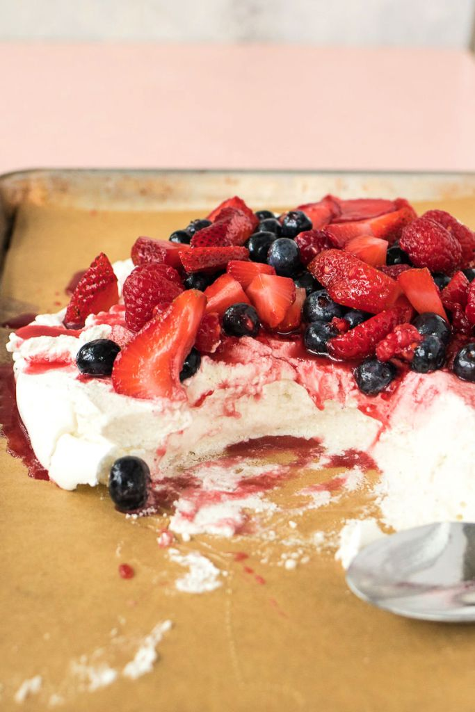 berry pavlova with bites removed and the center exposed