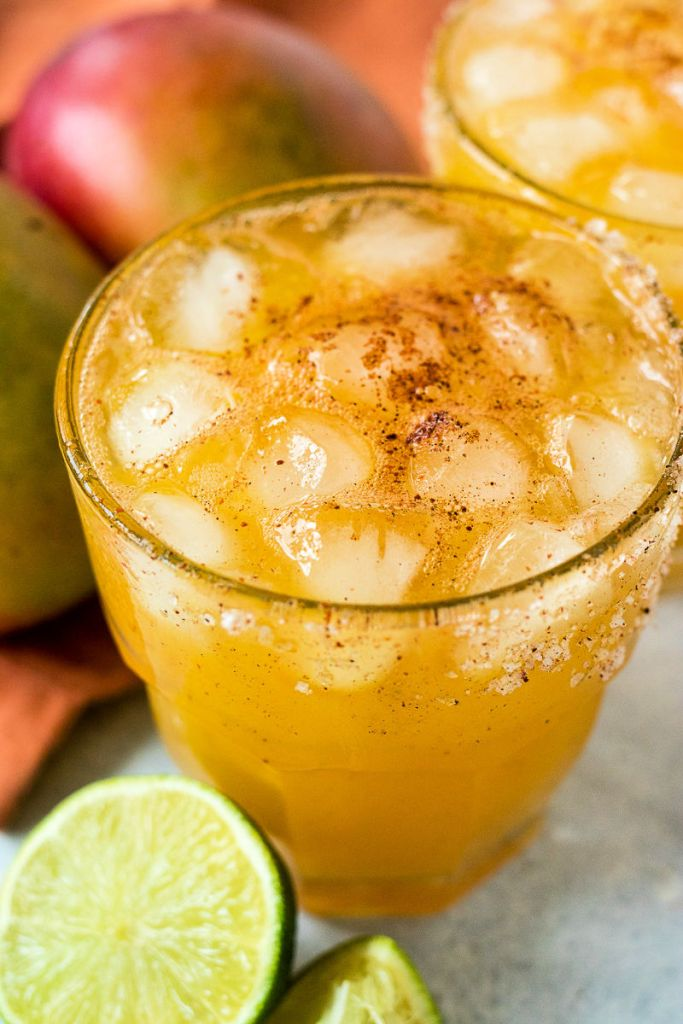 glass of chili mango margarita with a dusting of chili powder on top and a salt-rimmed glass
