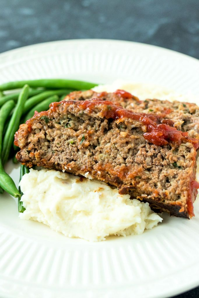 shot of sliced meatloaf on plate of mash potatoes and side of green beans (shot from the front of the plate)