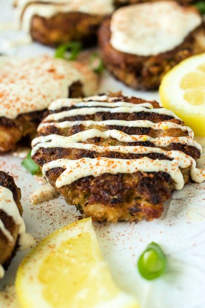 close up of shrimp crab cakes with a drizzle of garlic aioli