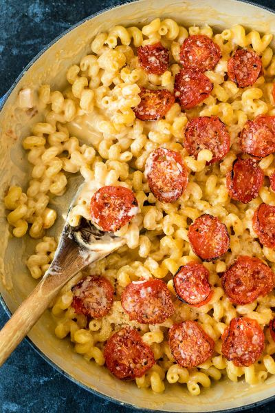 overhead shot of roasted tomato mac and cheese in a round casserole dish and a few servings removed