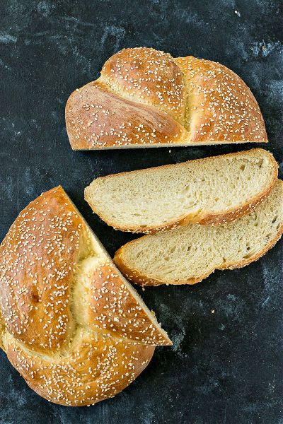overhead shot of sesame seed braided loaf partially sliced